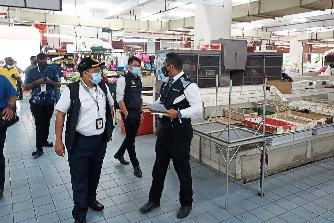 Health officers inspecting the market before closing it temporarily to allow disinfection work to be carried out.