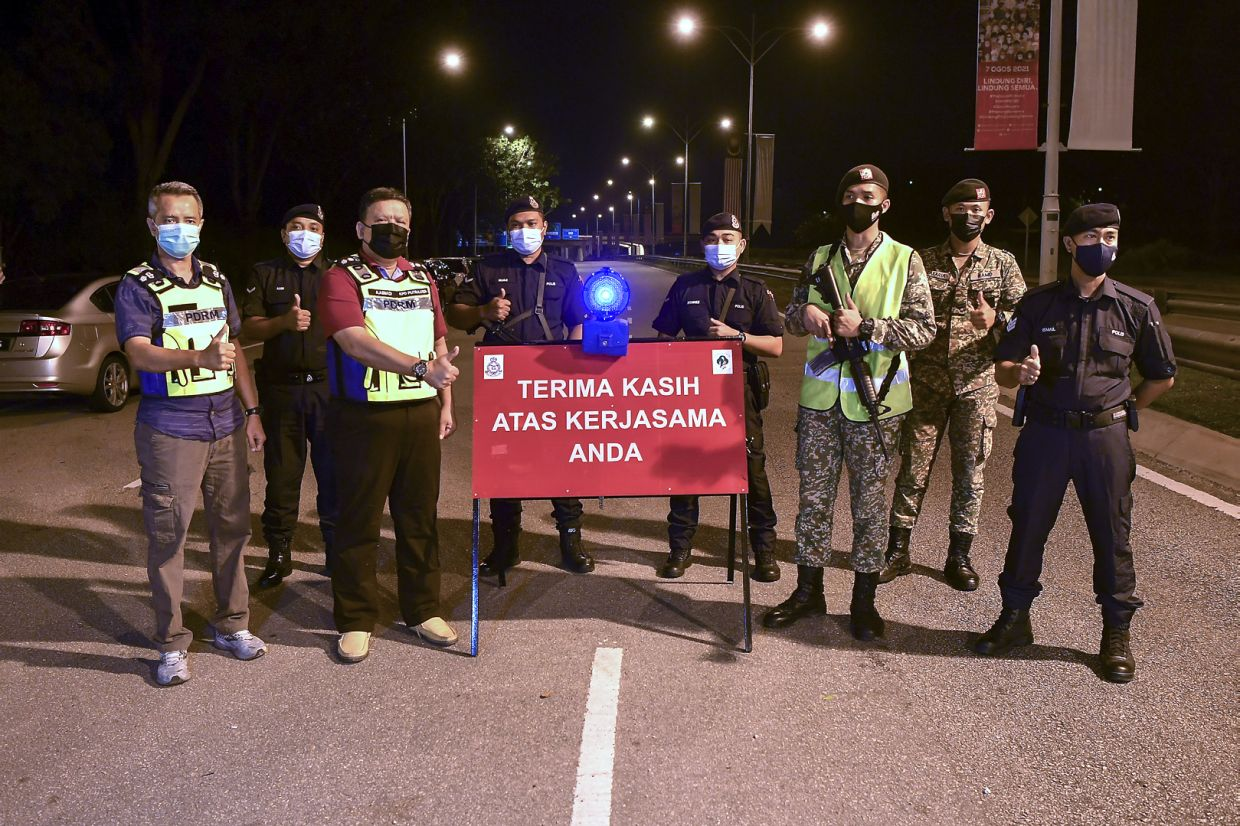 Putrajaya OCPD Asst Comm A. Asmadi Abdul Aziz (third from left) with police and army personnel after dismantling a roadblock in Putrajaya at midnight Thursday (Sept 9). - Bernama pic