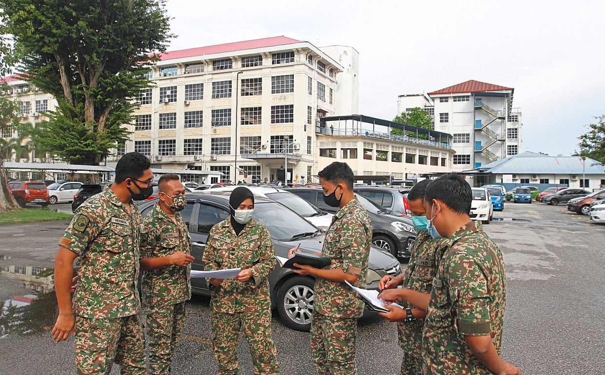 Second Infantry Division assistant director-general (health services) Lt Kol (Dr) Faira Rosmarina Mohd Rustam (with tudung) finalising matters on setting up the field hospital at Penang Hospital's car park.