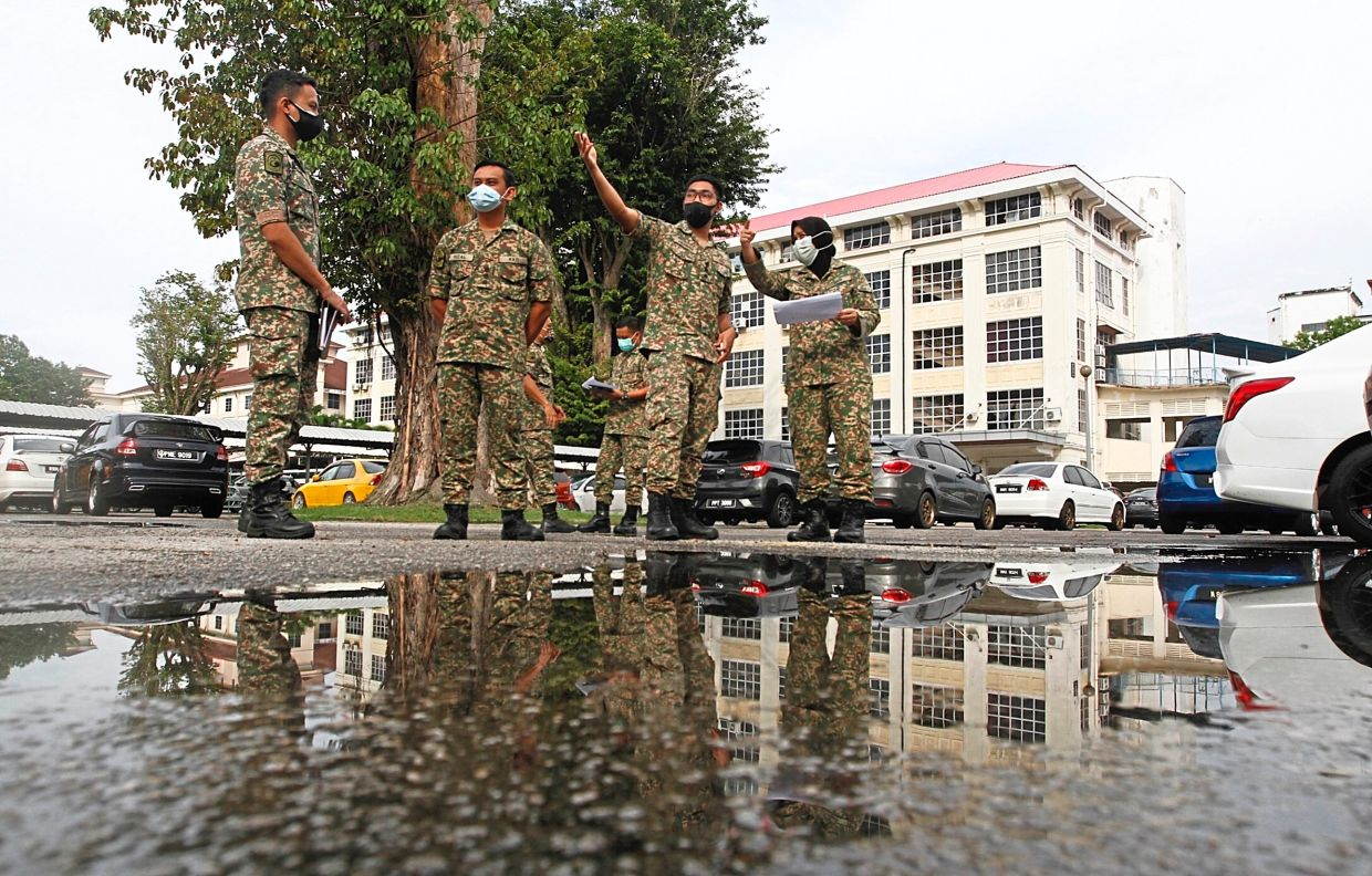 Getting organised: Second Infantry Division assistant director-general (health services) Lt Kol (Dr) Faira Rosmarina Mohd Rustam (right) and her officers plotting the layout of the facility to be set up at the car park of Penang Hospital in George Town. — ZHAFARAN NASIB/The Star