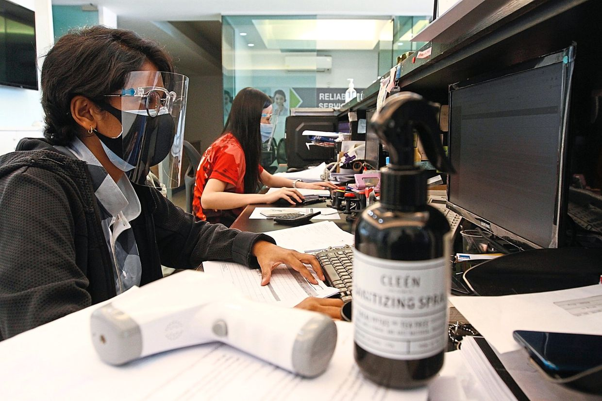 Workers in full protective attire such as double face masks and face shield.