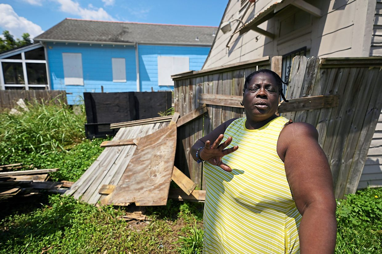 Kemp talking with a housing advocate in the aftermath of Hurricane Ida outside her rental home in the Lower Ninth Ward of New Orleans. Photos: Matt Slocum/AP