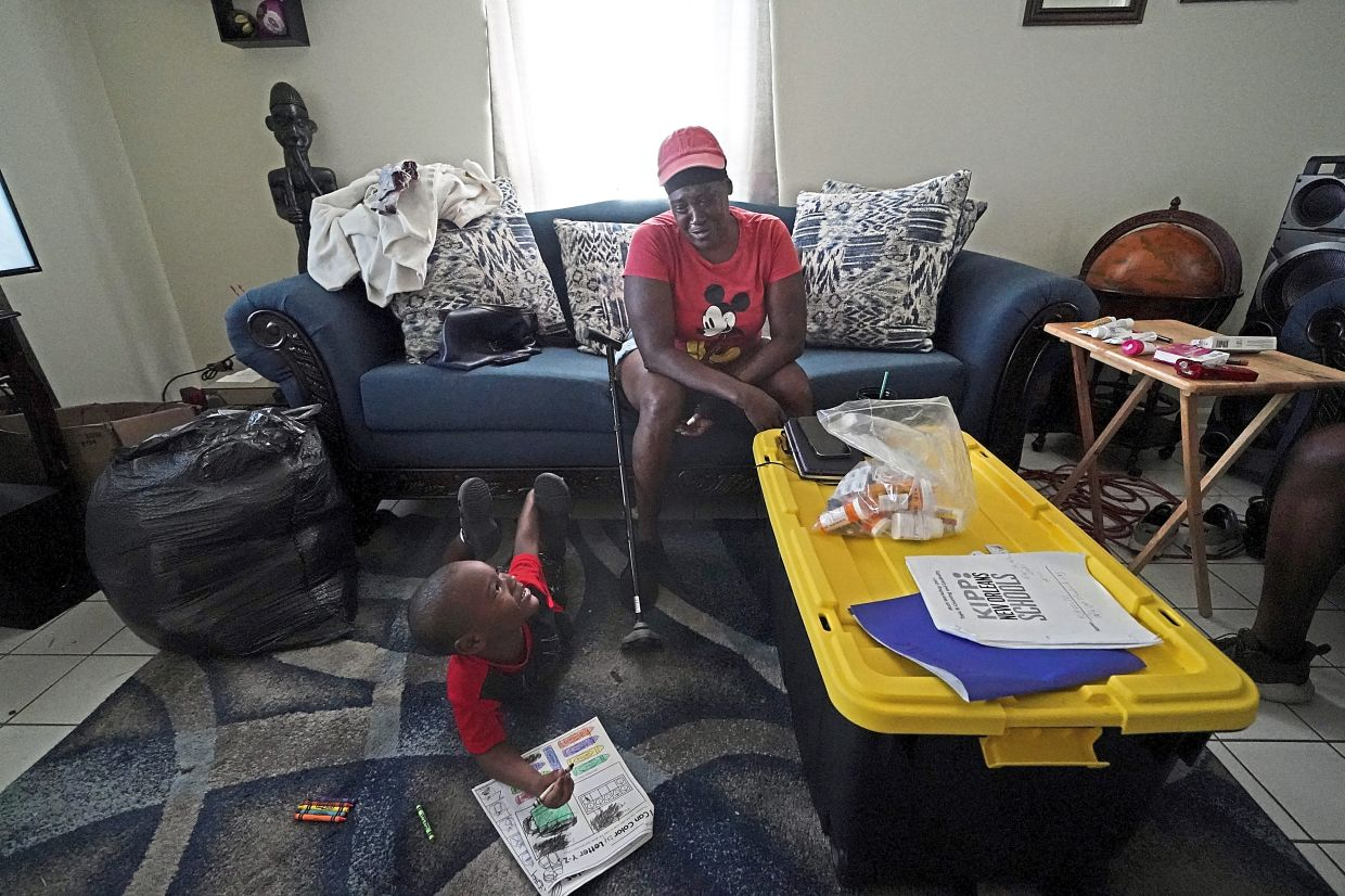 Blunt in her apartment with her grandson Kamille. Before the hurricane hit, the New Orleans native had hardly recovered from facing eviction and loss of her catering job during the pandemic.