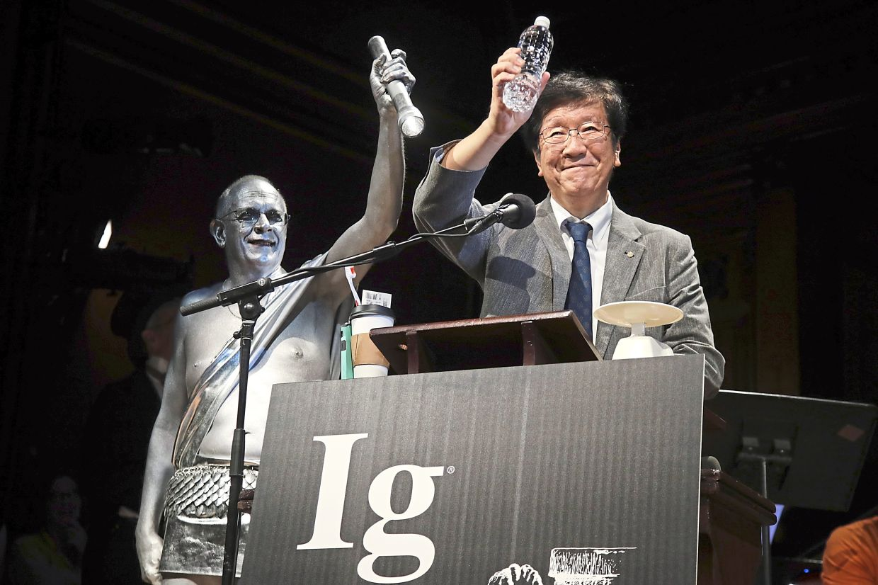 This file photo shows Shigeru Watanabe of Japan receiving the Ig Nobel award in chemistry for estimating the total saliva volume produced per day by a typical five-year-old at the 29th annual Ig Nobel awards ceremony at Harvard University.