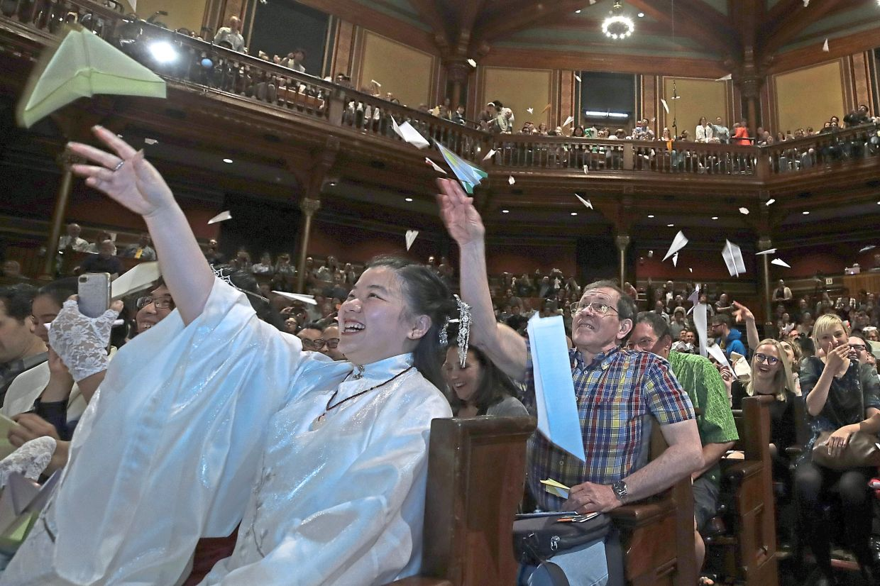 In this file photo, audience members toss paper airplanes at the 29th annual Ig Nobel awards ceremony at Harvard University. The spoof prizes for weird and sometimes head-scratching scientific achievement will be presented online in 2021 due to the coronavirus pandemic.