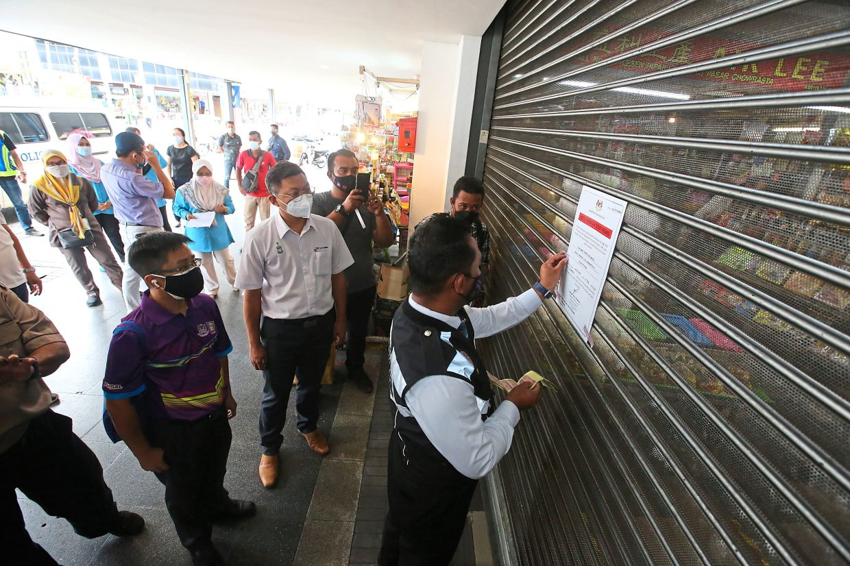 Teh (in white) looking on as a health officer puts up the closure notice in front of the Chowrasta Market.