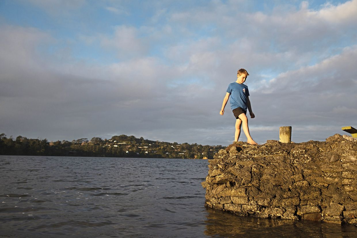 Jago Haag, 9, plays at the water's edge at sunset in Auckland.
