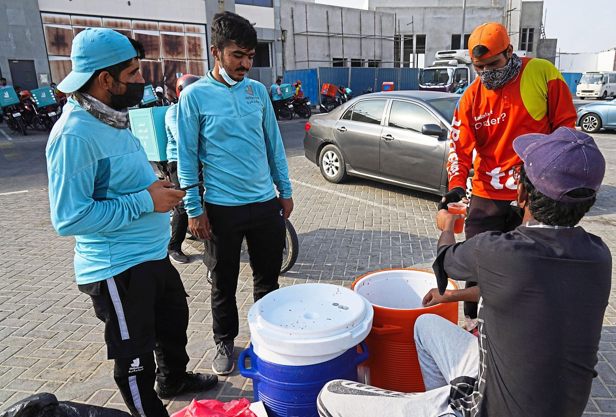 Motorcycle delivery drivers taking a break and buying juice in Dubai.