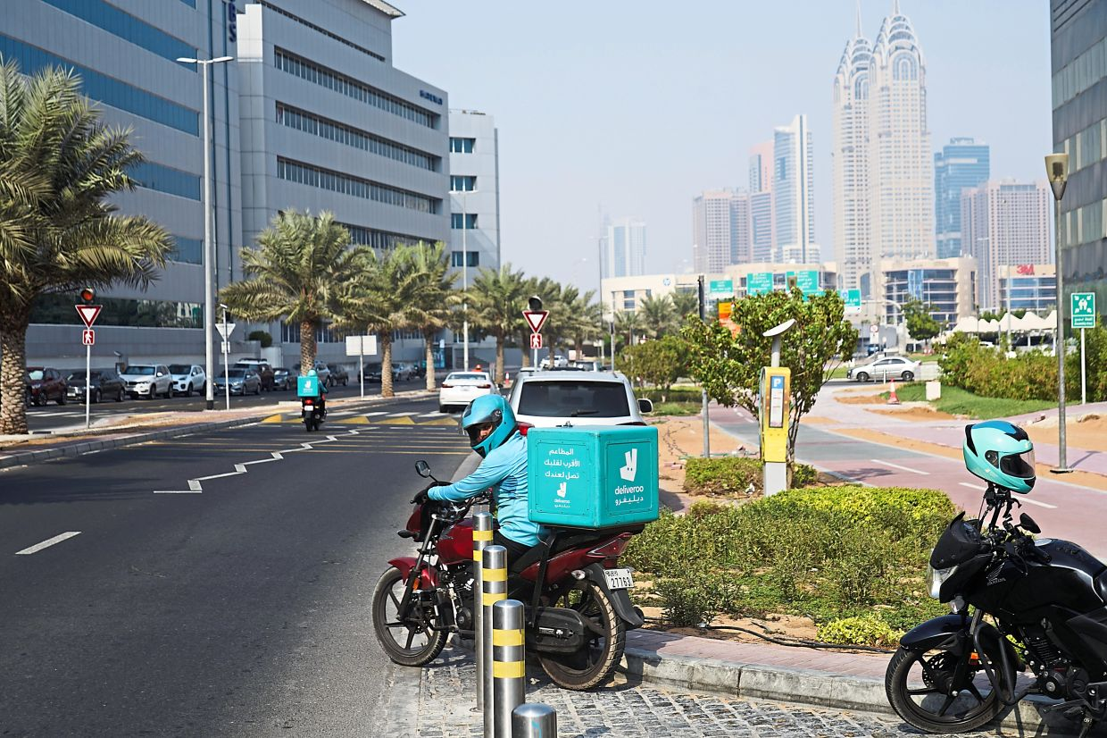 A delivery driver for the app Deliveroo prepares to make a delivery in Dubai.
