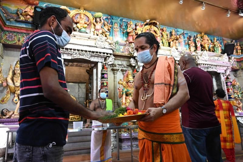 A migrant worker receives a blessing from a Hindu priest during a visit to the Sri Veeramakaliamman temple in the district of Little India in Singapore on September 15, 2021, after the introduction of a programme to let the workers, who have had restrictions imposed on their movements and activities as a measure to prevent the spread of Covid-19 coronavirus, visit various predetermined areas in the community. - AFP