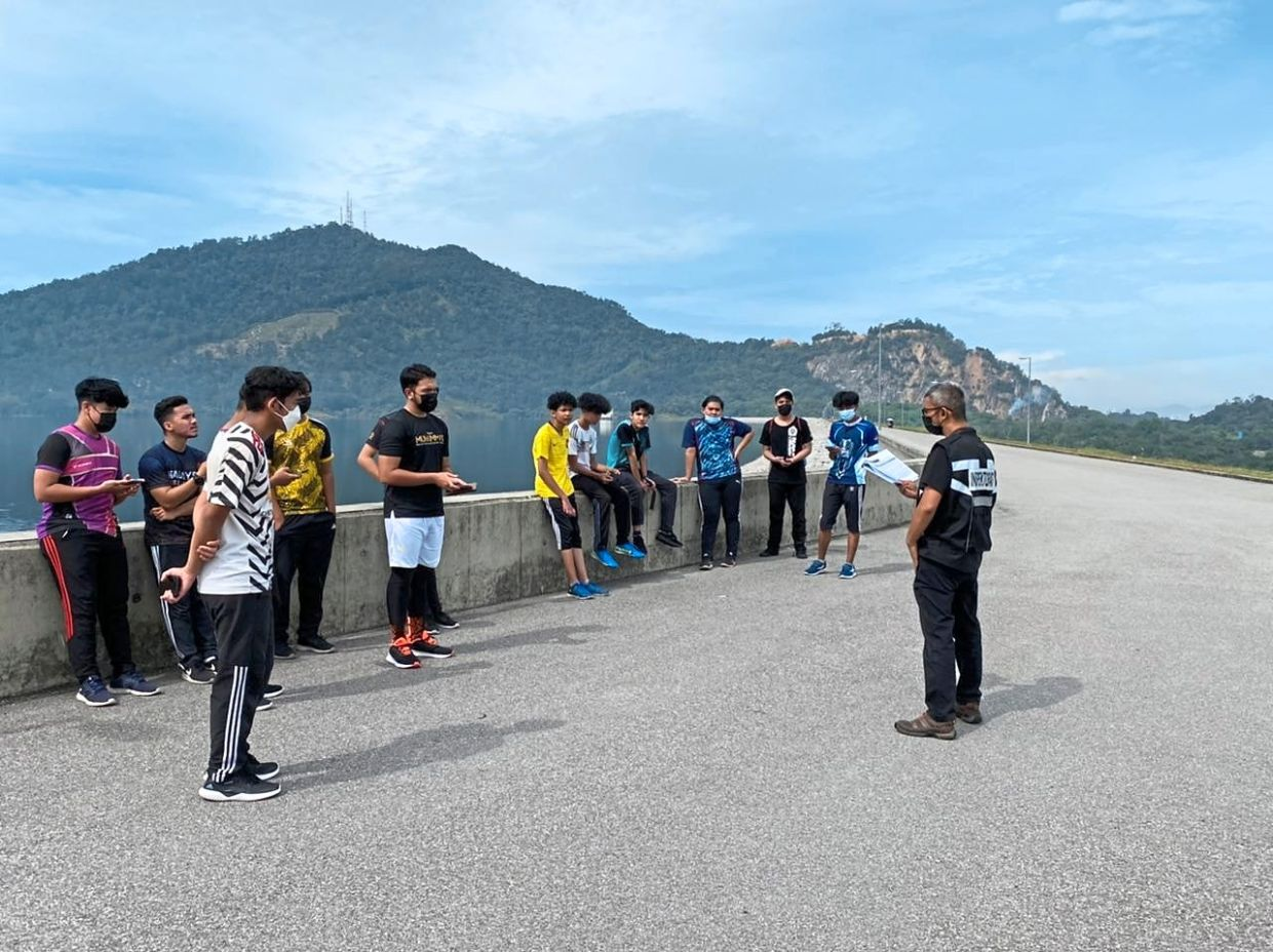 Busted: An enforcement officer issuing summons to visitors in Mengkuang Dam for SOP violation. — Photo taken from social media