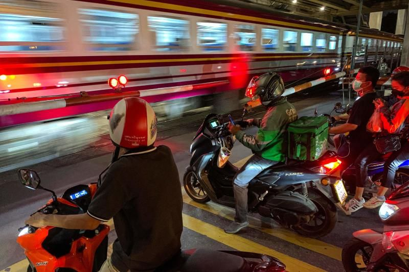 Motorists wait for a commuter train to pass through a crossing in Bangkok on Wednesday (Sept 15, 2021.