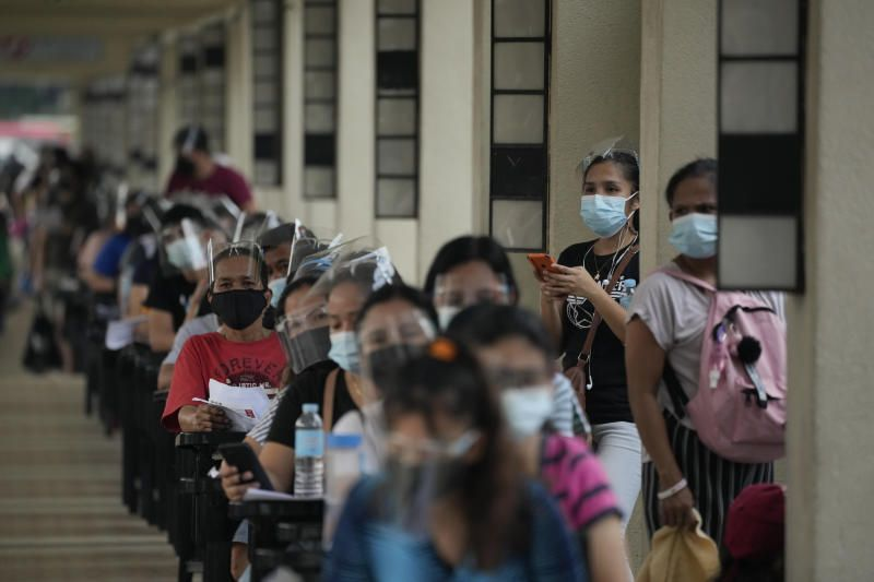 Residents wait for their turn at a vaccination center in Quezon city, Philippines. The government continues to urge Filipinos to get vaccinated as Covid-19 cases keep rising in the country. - AP