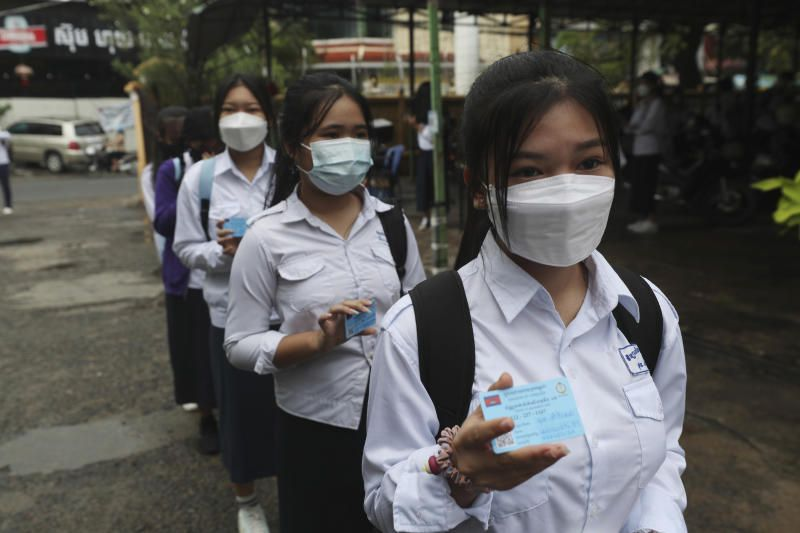Students show off the COVID-19 vaccination pass before their morning classes at the Preah Sisowath high school, in Phnom Penh, Cambodia, Wednesday, Sept. 15, 2021. The Municipal of Phnom Penh recently issued a statement to reopen junior high and high schools due to the high number of vaccination rates for teachers and students, low infection rates and the schools' to compliance to health standards. - AP