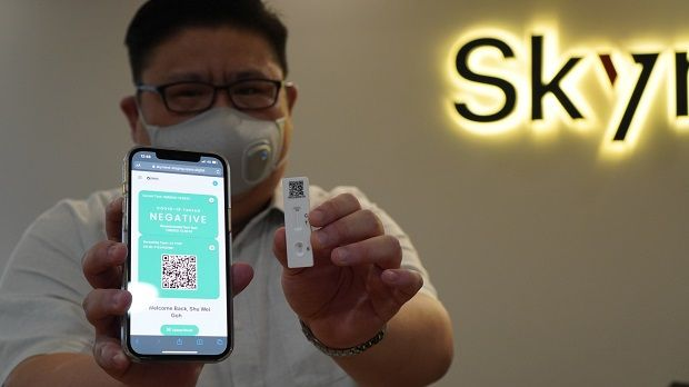"""""""We still need to remain vigilant about the spread of the virus,"""" said AxialHealth founder Shawn Tan, shown here demonstrating how the Vpass works."""