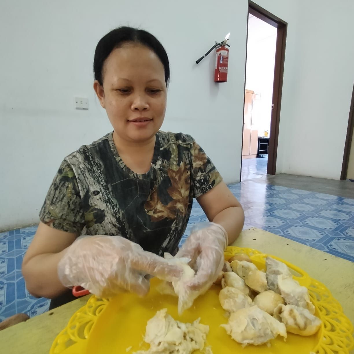 Alang Shana, from Chenderiang, removing durian flesh from the seeds to make tempoyak.