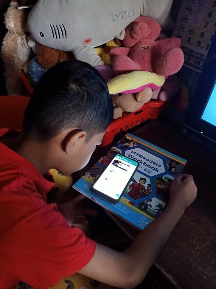 A child uses a phone to access MYReaders reading resources.
