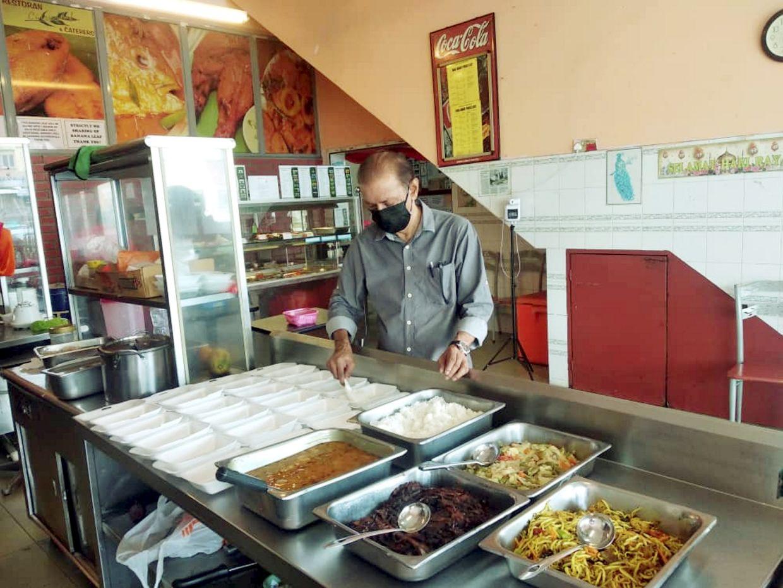 Thanabalan preparing food packs at his restaurant in Seremban for distribution to migrant workers in Alor Gajah, Melaka.