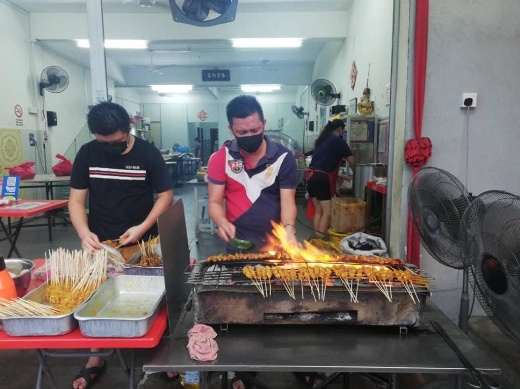 Long preparing satay for his customers who are facing hardship.