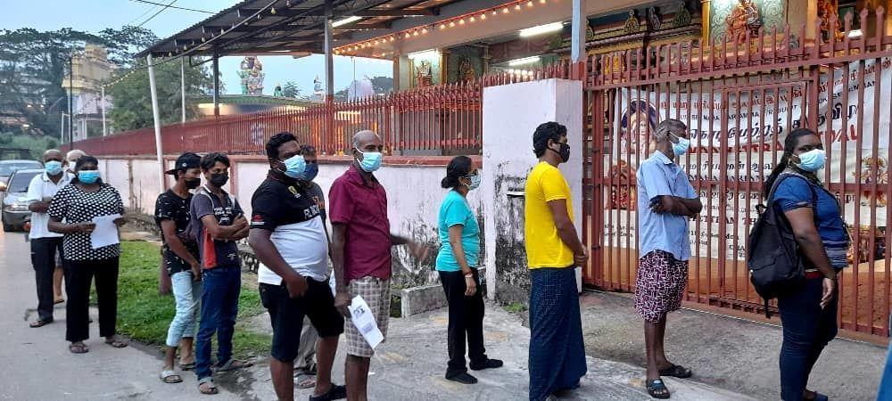Members of the public queuing to get food at the Sri Maha Mariamman Temple in Bukit Tembok, Seremban