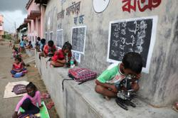 In remote Indian village, teacher turns walls into blackboards to close school gap