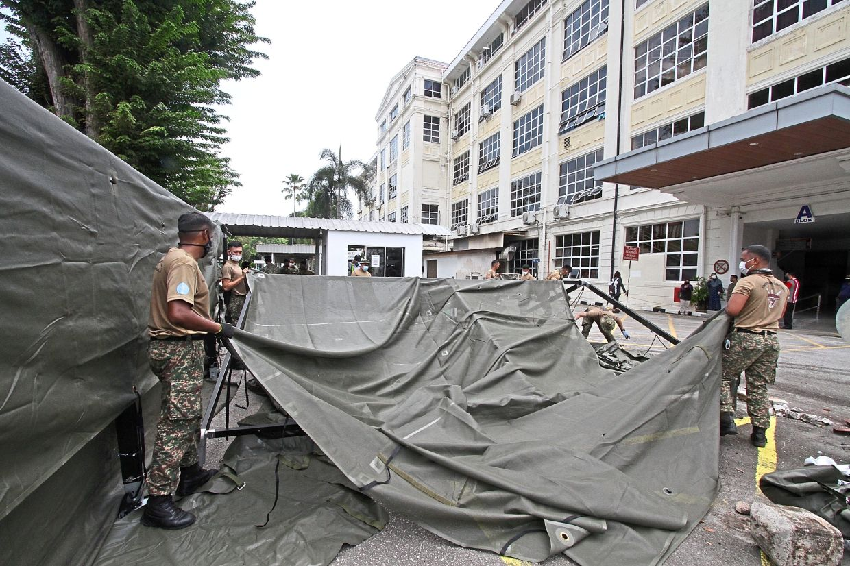 (Above and below) Army personnel busy setting up the tents.