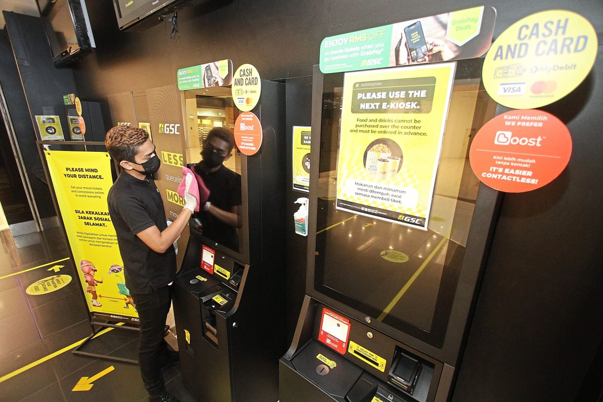 A staff member wiping the e-kiosk meant for buying tickets as well as food and beverages.
