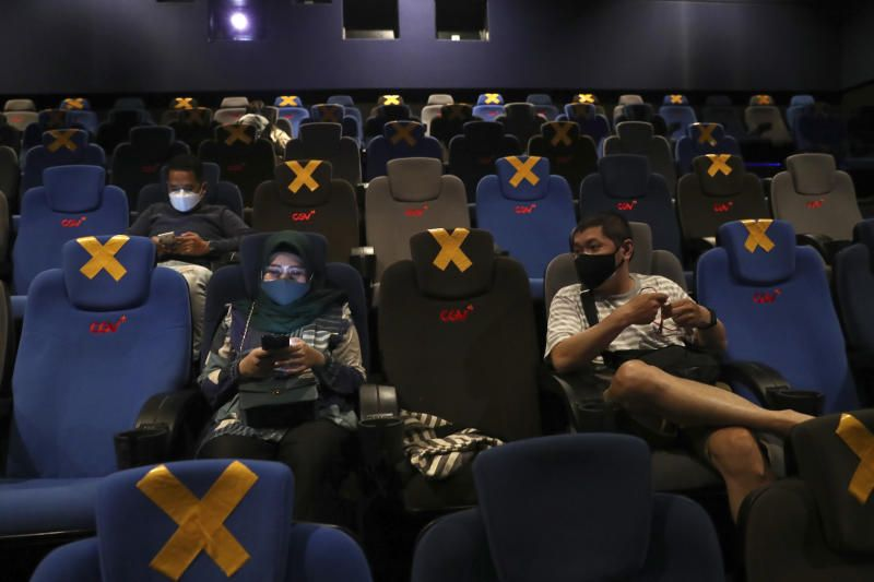 People sit amid physical distancing markers before the start of a movie show during the first day of reopening at a cinema in Jakarta, Indonesia, Thursday, Sept. 16, 2021. Cinemas in several cities shut during the deadly wave of coronavirus outbreak that hit the country in July were allowed to begin reopening with capacity limit as cases decline. - AP