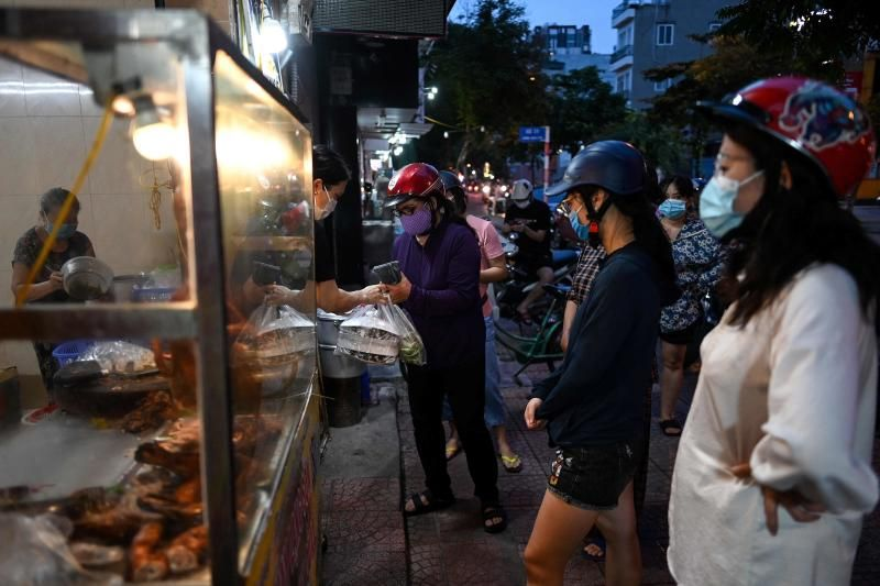 Women wearing face masks observe social distancing while waiting outside an eatery in Hanoi on Tuesday, Sept 16, 2021, following the resumption of take-away food services after they were shuttered for nearly two months due to Covid-19 coronavirus restrictions. - AFP