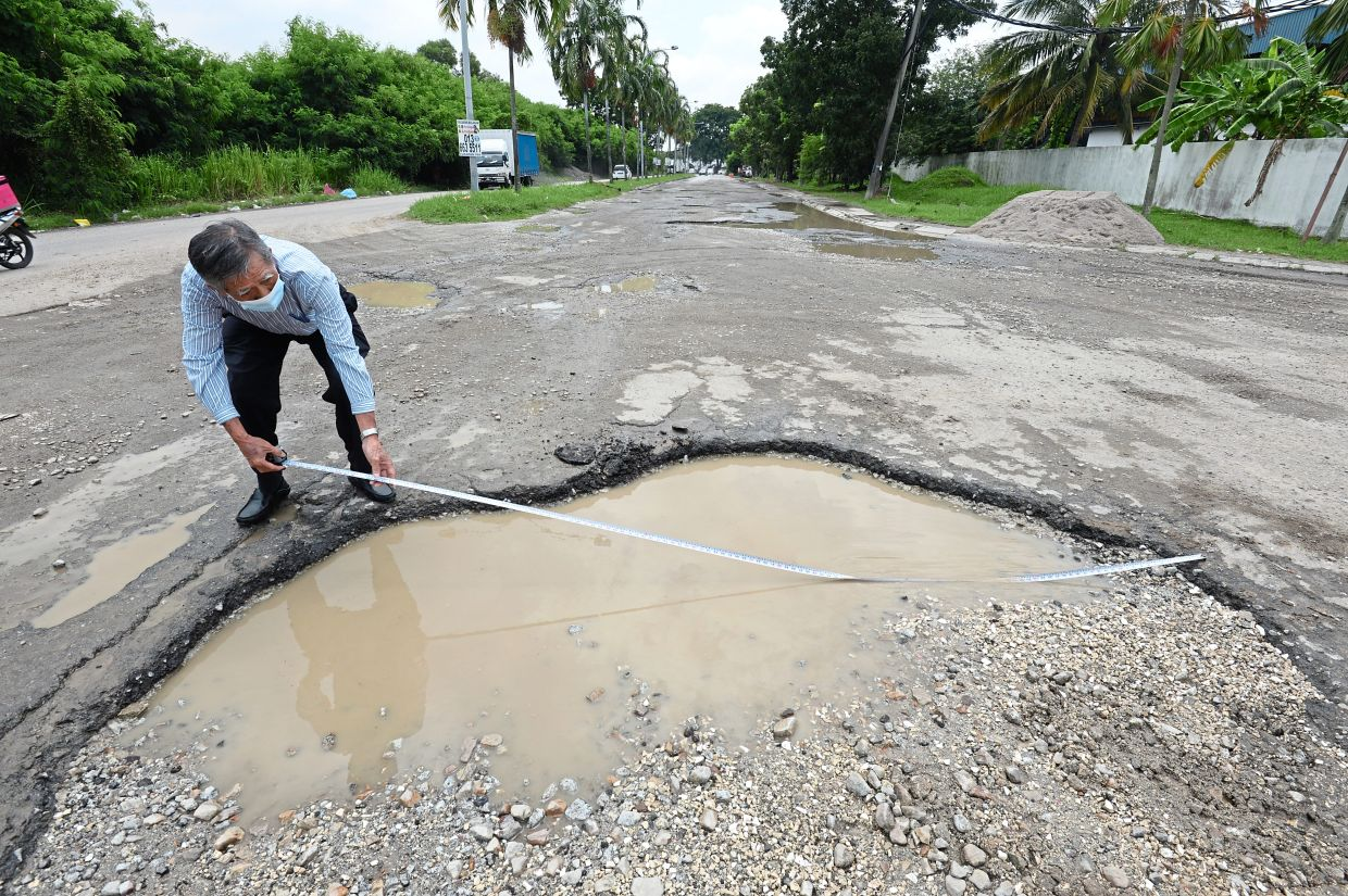Mok showing the width of one of the large potholes in Jalan Sungai Kapar Indah, which measures between 3.2m and 4.1m. — Photos: S.S. KANESAN