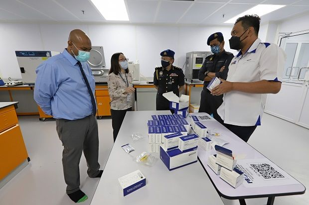 Mohd Ridzuan (right) and his officers checking the self- test kits at the factory. With him are (from left) Ariff and Lim. — LIM BENG TATT/The Star
