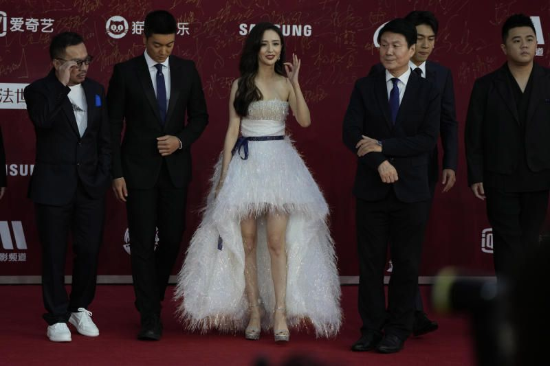 Actress Tong Liya gesturing with the crew and cast of the movie Flashover during the red carpet for the 11th Beijing International Film Festival held on the outskirts of Beijing, China, Monday, Sept. 20, 2021. - AP