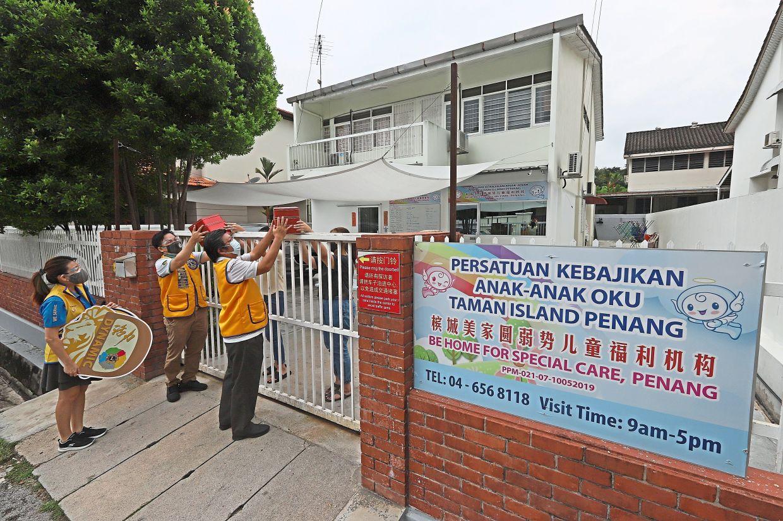 Lions Club members handing over mooncakes for the children at Persatuan Kebajikan Anak-Anak OKU Taman Island.