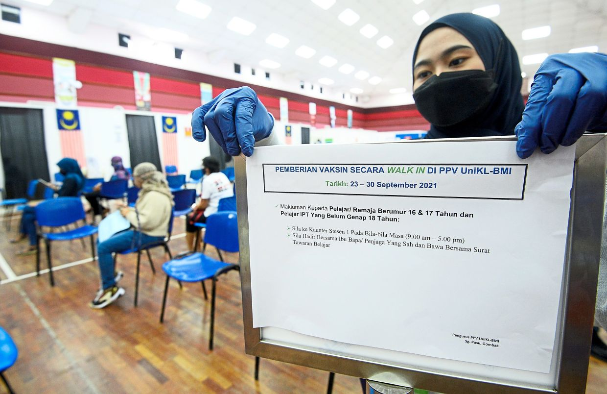 All set for teens: UniKL-British Malaysia Institute PPV staff member Atirah Cik Rozman placing a walk-in vaccination notice for teenagers at the centre in Gombak. — AZHAR MAHFOF/The Star