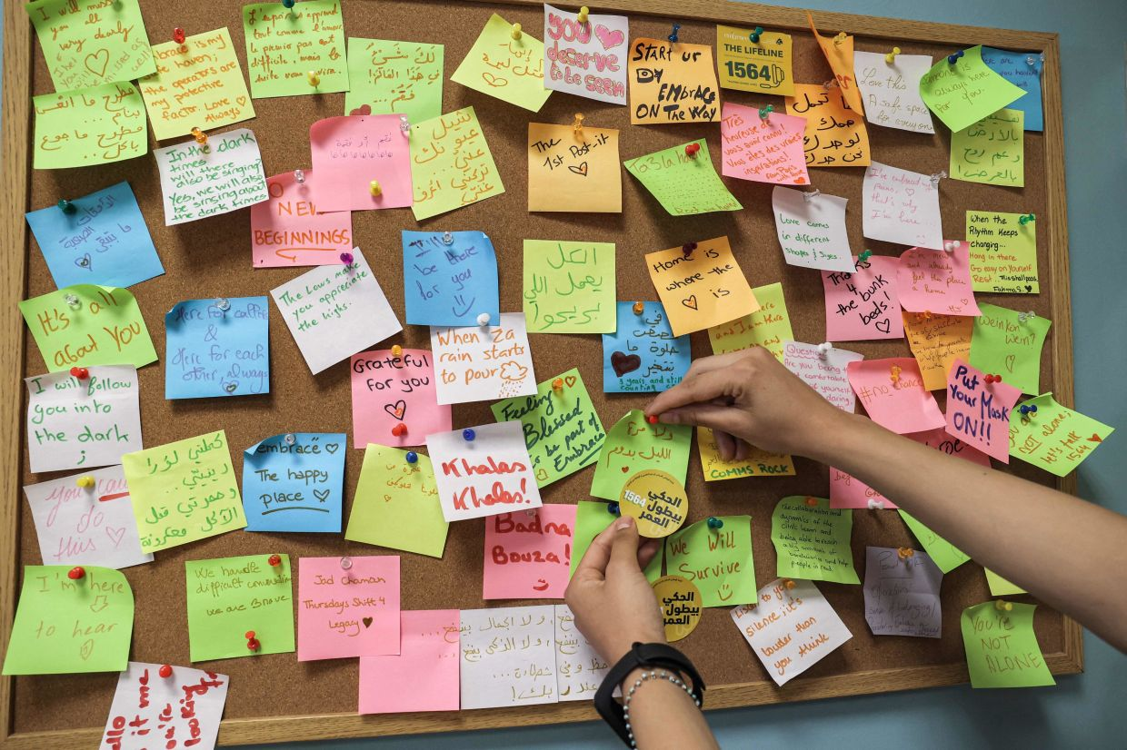 A woman places a note on a post-it board at the offices of Embrace, an NGO which runs a suicide-prevention hotline, in Beirut.