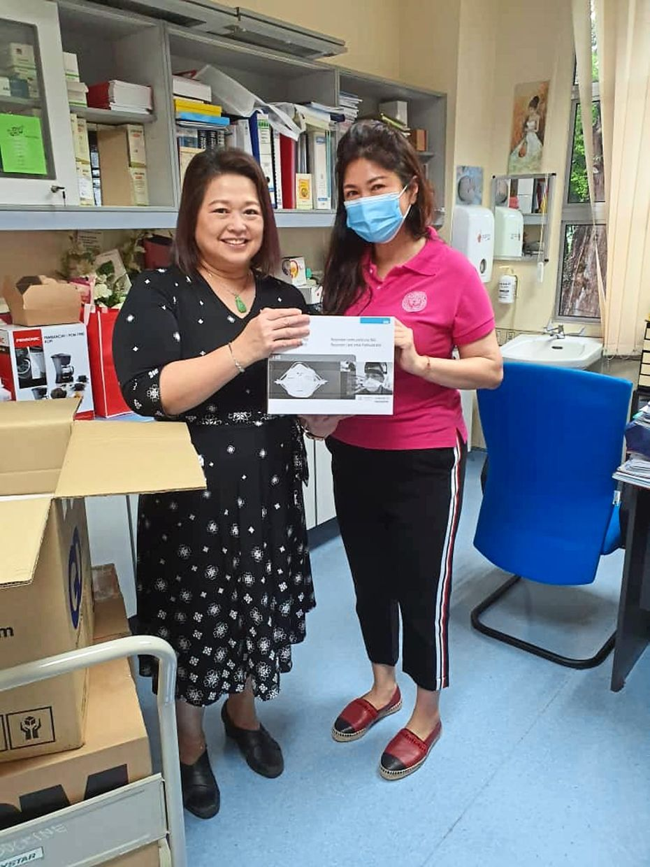 SI Penang immediate past president Michelle Lim (in pink) handing over masks to Penang Hospital infectious disease unit head Datuk Dr Chow Ting Soo.