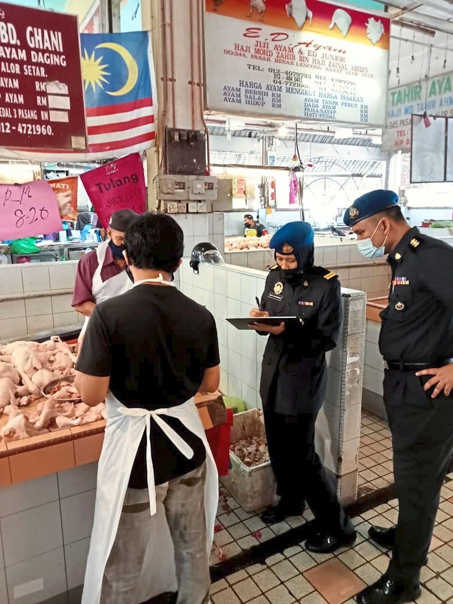 Enforcement officers checking on chicken meat prices at a wet market in Alor Star.