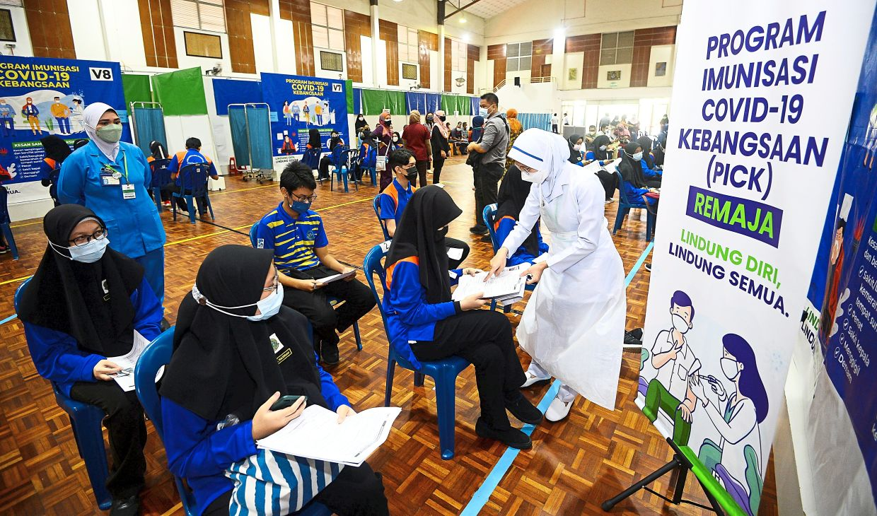 While students aged 12 and above are eligible to receive the Covid-19 vaccine, younger ones are not, thus the adults around them should be fully vaccinated to help protect them. — AZHAR MAHFOF/The Star