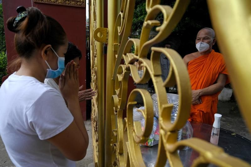 People offering food and alms to a Buddhist monk as they pray during the Pchum Ben festival (Festival of Death) outside a pagoda in Phnom Penh on Friday (Sept 24, 2021), as authorities halted celebrations of the festival after a Covid-19 coronavirus outbreak among monks in the capital. - AFP