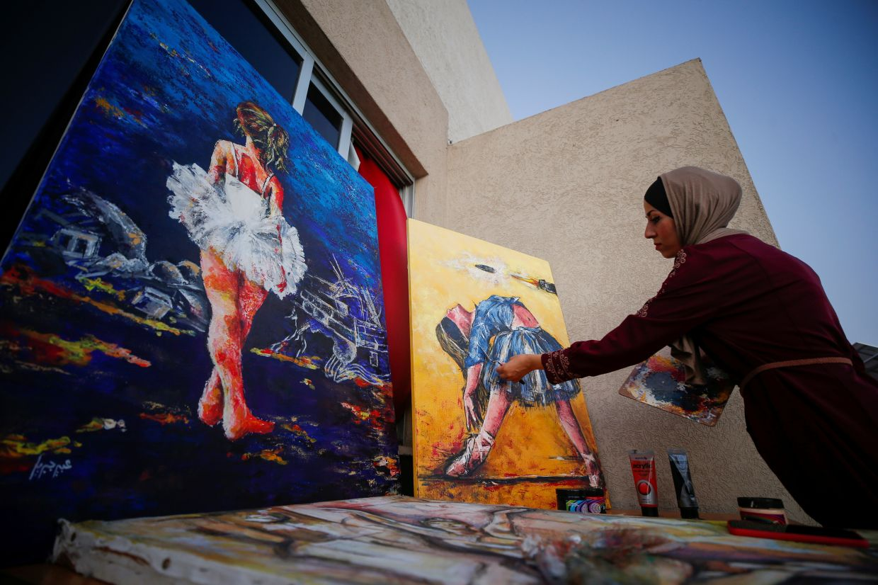 Jebril works on ballet paintings at her home in Gaza. Photo: Reuters