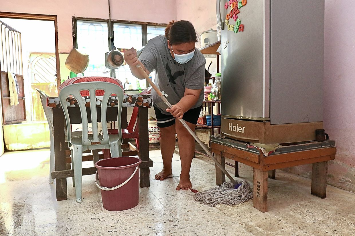 Shiesylia mopping the kitchen floor in her home after the latest flash flood.