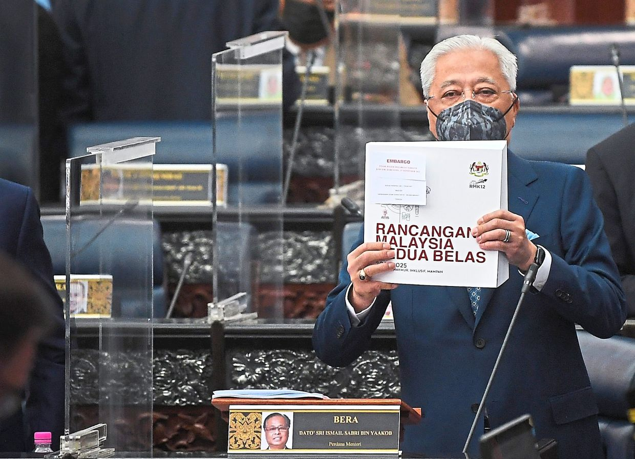 On the table: Ismail Sabri holding up the 12th Malaysia Plan during the Parliament session in Kuala Lumpur. — Bernama