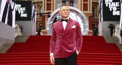 Daniel Craig walks red carpet for final time as James Bond in rain-swept London