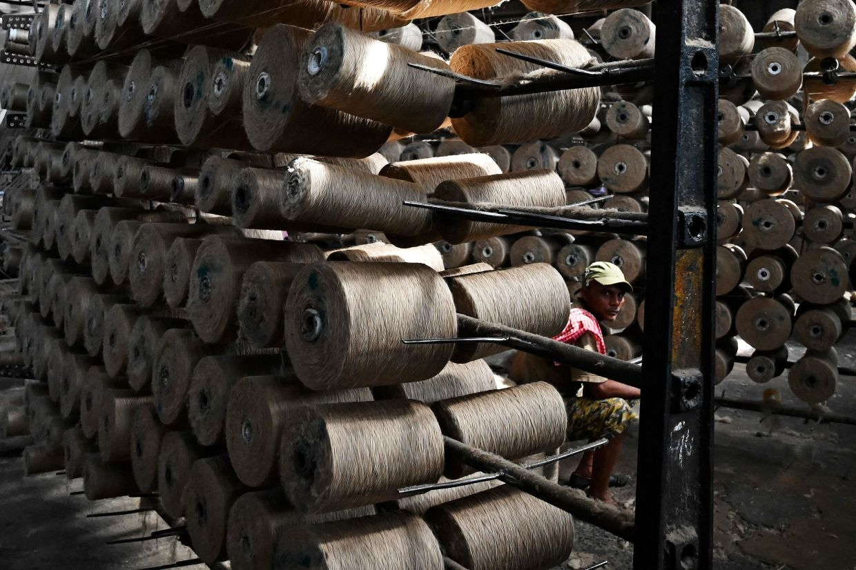 A labourer takes a break as he works at a private jute mill in Jagatdal. Photo: AFP