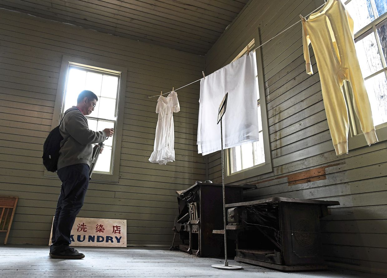 A man taking a photo of old stoves in the restored 1917 Chinese laundry building at Wawona in Yosemite National Park.