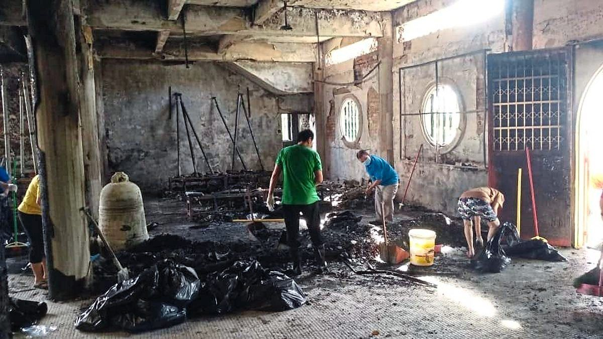 Covered in soot: Volunteers cleaning the affected area after the fire at Kek Lok Si Temple.