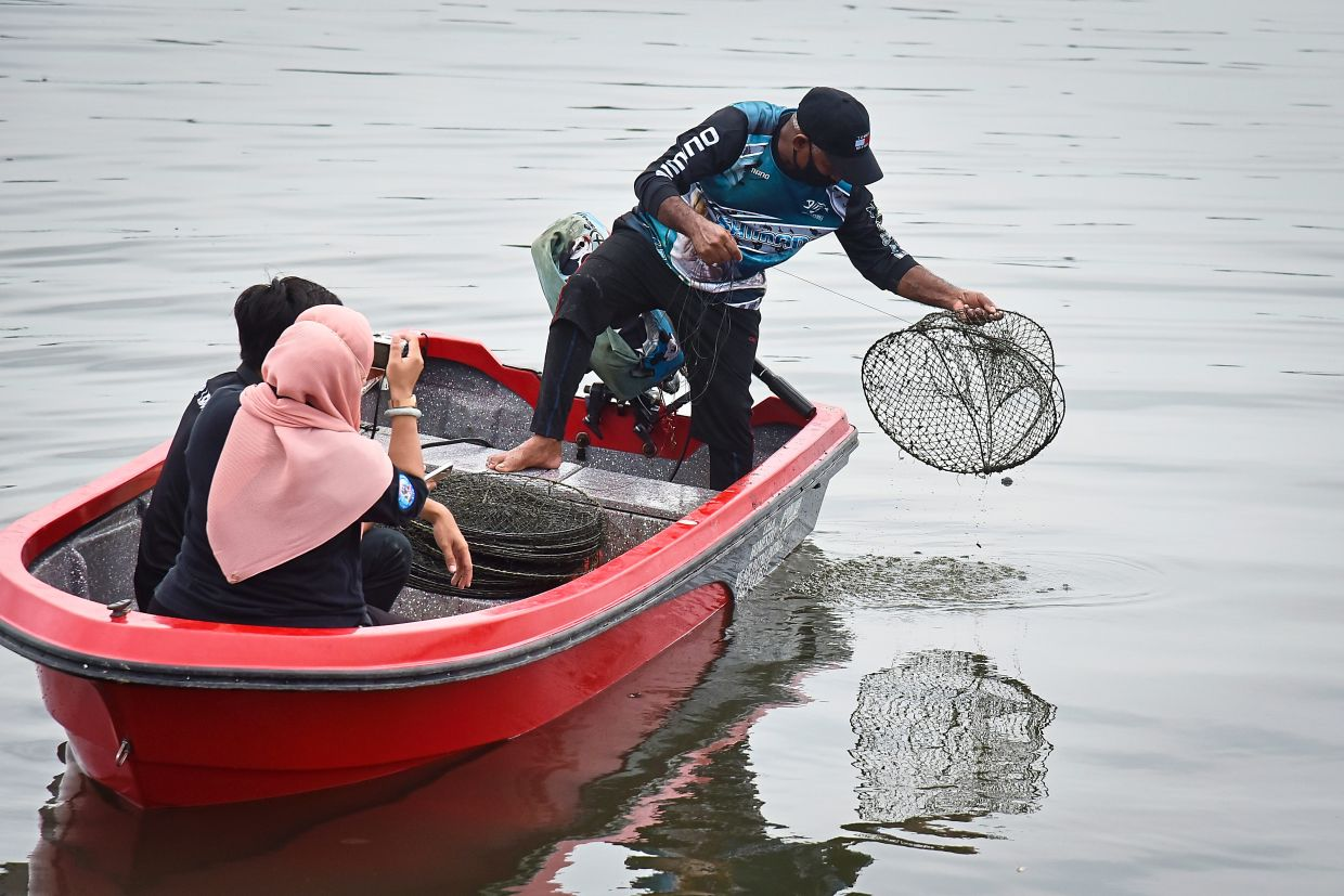 Show and tell: Homestay owner Karim Abdullah showing visitors how to set a crab trap (bintur) at Kampung Air Tradisi Patau-Patau in Labuan. This activity has become one of the main attractions for tourists and homestay visitors in the water village. — Bernama