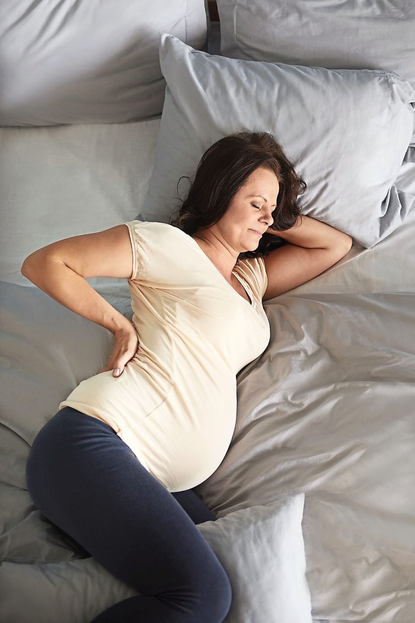 Sleeping on your side with a pillow between your legs to bring your knee to the same height as your hip can help relieve back pain caused by pregnancy.  - gpointstudio / Freepik